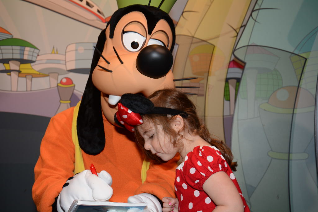 Watching carefully as Goofy signs her autograph book